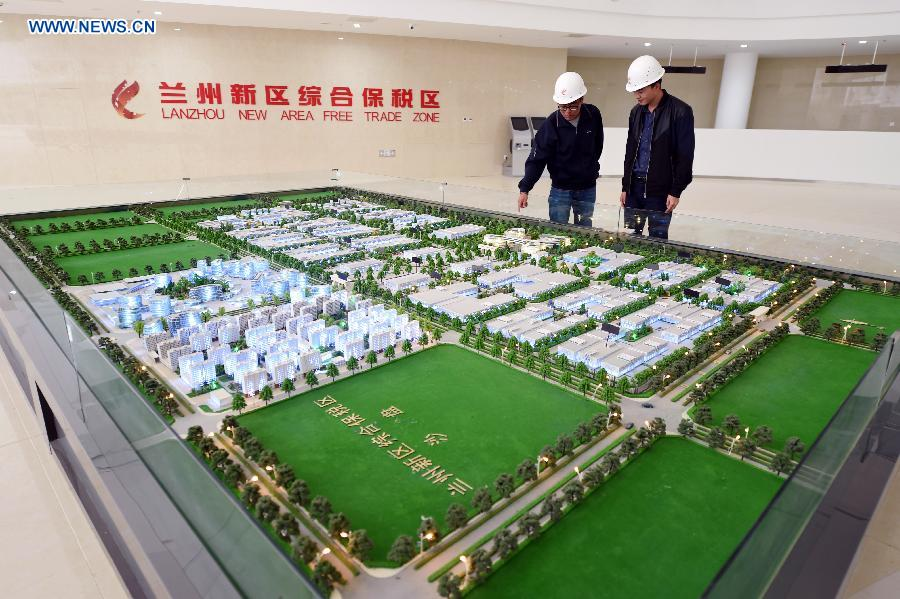 Workers look at the sand table of the Lanzhou New Area Free Trade Zone in Lanzhou, capital of northwest China's Gansu Province, Aug. 18, 2015.