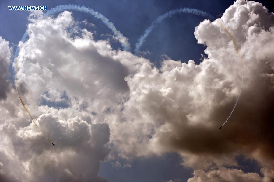 Two aircraft show aerobatics, making a formation in the shape of a heart from a trail of smoke at the 2015 Shenyang Faku International Flight Convention, in Faku County of Shenyang, capital of northeast China's Liaoning Province, Aug. 21, 2015.