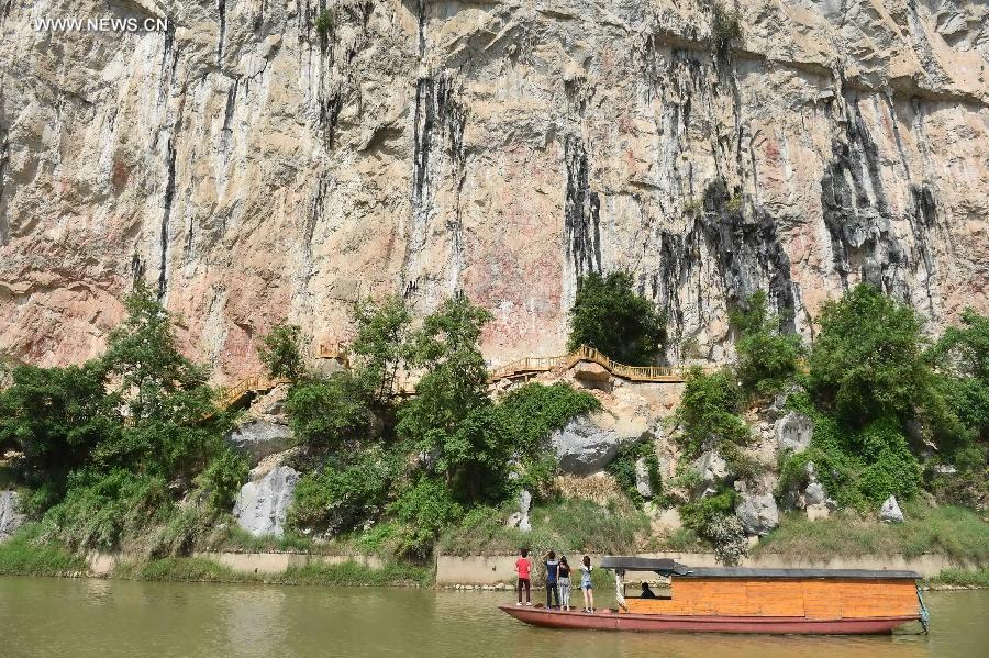 Tourists view Huashan rock paintings on the cliffs along the Mingjiang River, a tributary of the Zuojiang River, in Ningming County of Chongzuo City, southwest China's Guangxi Zhuang Autonomous Region, Aug. 20, 2015.
