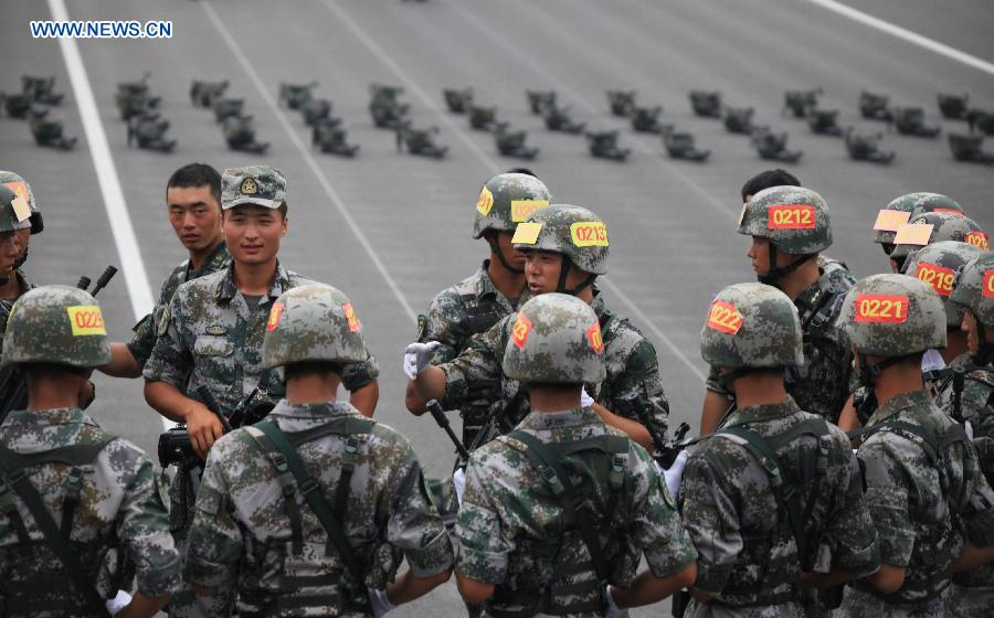 Photo taken on July 28, 2015 shows soldiers communicate with each other during training for the Sept. 3 military parade at the parade training base in Beijing.