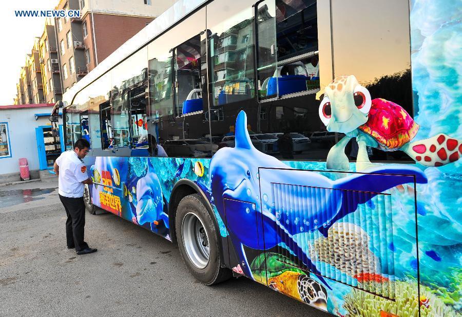 Bus driver Gu Zhenyu cleans his ocean theme bus in Changchun, northeast China's Jilin Province, Sept. 14, 2015.