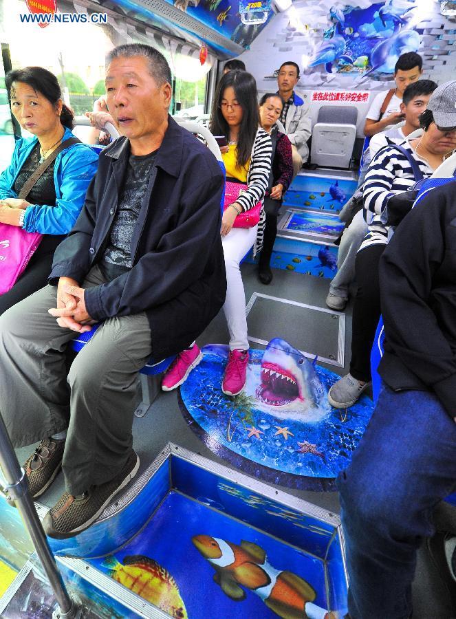 Passengers take an ocean theme bus in Changchun, northeast China's Jilin Province, Sept. 14, 2015.