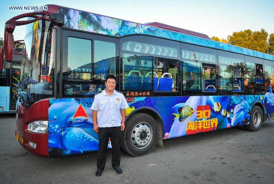 Bus driver Gu Zhenyu poses for a photo with his ocean theme bus in Changchun, northeast China's Jilin Province, Sept. 14, 2015.