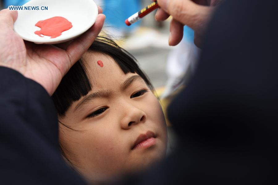 A girl gets a red dot on her forehead (which is called opening the wisdom eye) during a first writing ceremony in Guiyang, capital of southwest China's Guizhou Province, Sept. 28, 2015.