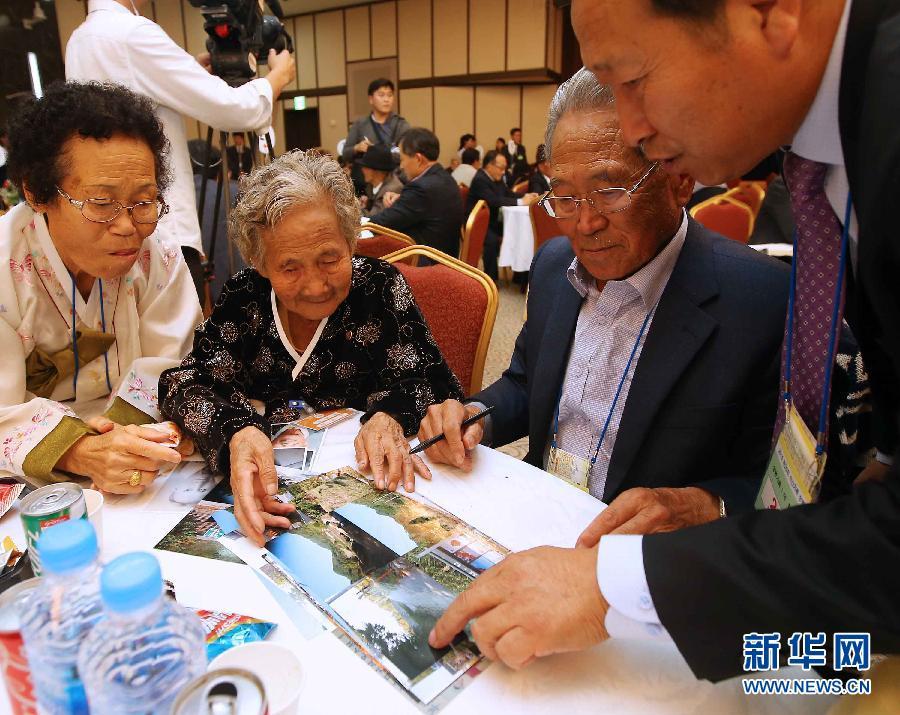 10月20日,在朝鲜金刚山离散家属会面所,韩国亲属向84岁的朝鲜奶奶李兰溪(音译)(左二)展示她家乡韩国忠州的照片。当日,韩国和朝鲜在朝鲜金刚山景区启动第20次离散家属团聚活动。这是自去年2月以来,朝韩首次举行离散家属团聚活动。 新华社/韩联社