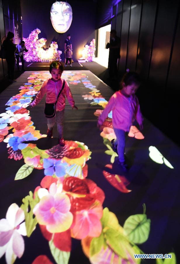 Children experience an interactive projection installation by a Taiwanese floral artist at the 2015 Taipei International Flower Design Award show in Taipei, southeast China's Taiwan, Oct. 31, 2015.