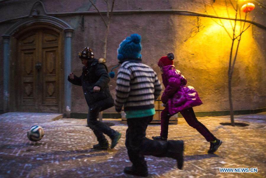 Children play football on a street in the old town of Kashgar, northwest China's Xinjiang Uygur Autonomous Region, Dec. 18, 2015.