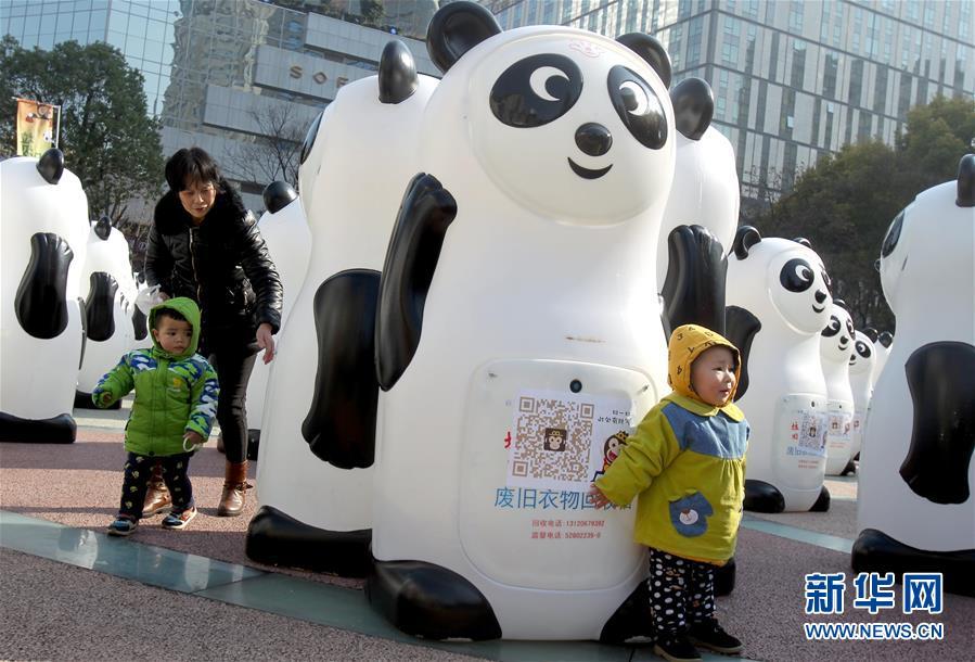 1月8日,小朋友跟熊猫回收箱合影。新华社记者刘颖摄