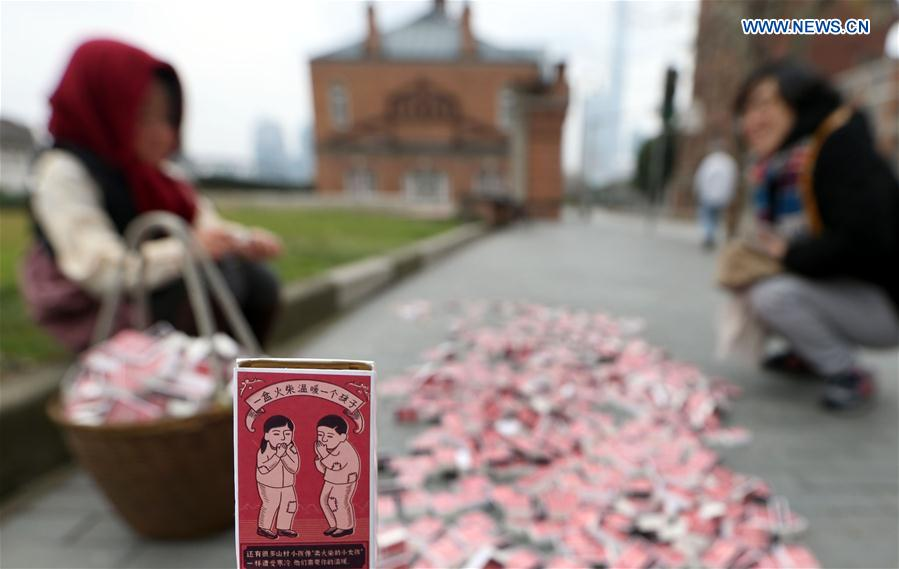 A match box is seen against the backdrop of the 'little match girl' at Waitan area in Shanghai, east China, Jan. 12, 2016.