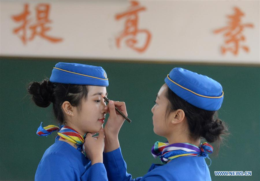 A student pencils the eyebrows for her classmate in training class at Bishan Vocational Education Center in Chongqing, southwest China, Jan. 13, 2016.