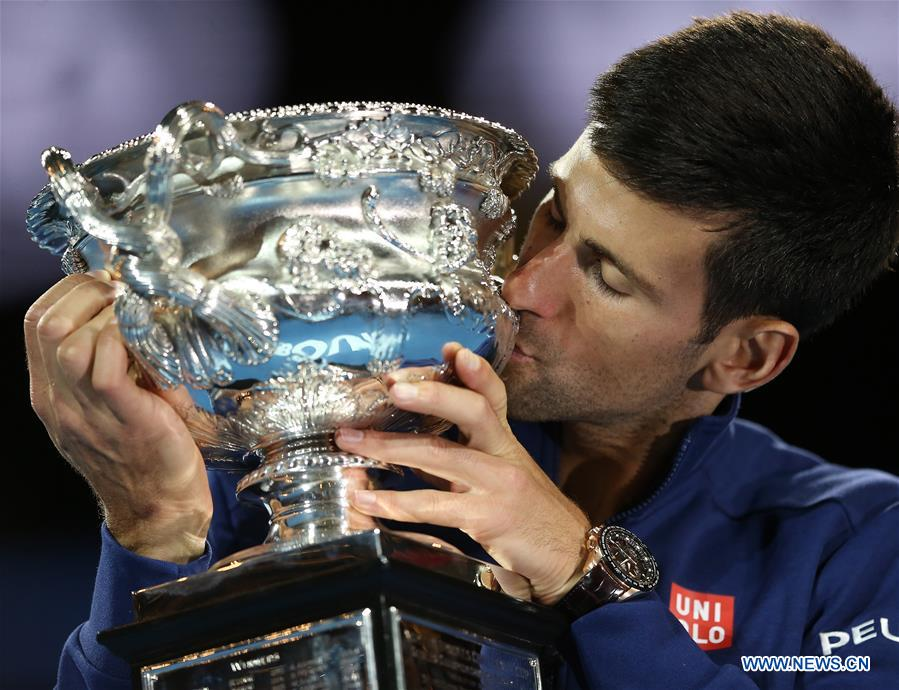 Novak Djokovic of Serbia poses with the trophy after winning the final of men's singles against Andy Murray of Great Britain at the Australian Open Tennis Championships in Melbourne, Australia, Jan. 31, 2016. Novak Djokovic won the match 6-1, 7-5, 7-6.