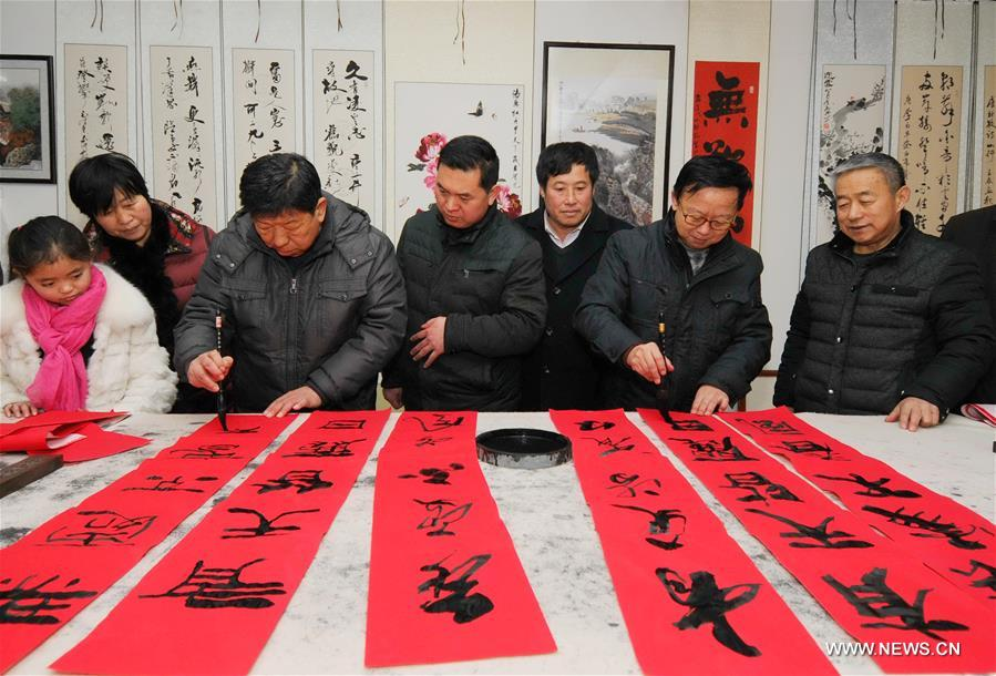 Calligraphy enthusiasts write couplets to greet the Spring Festival in Guangzong County of north China's Hebei Province, Jan. 31, 2016
