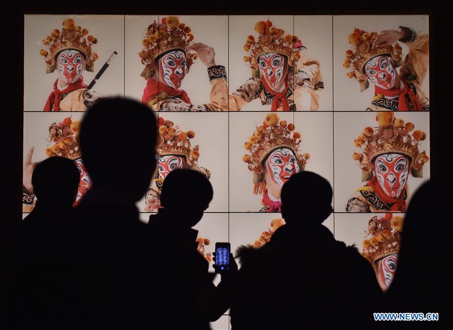 Visitors view pictures at the Capital Museum in Beijing, capital of China, Feb. 1, 2016.