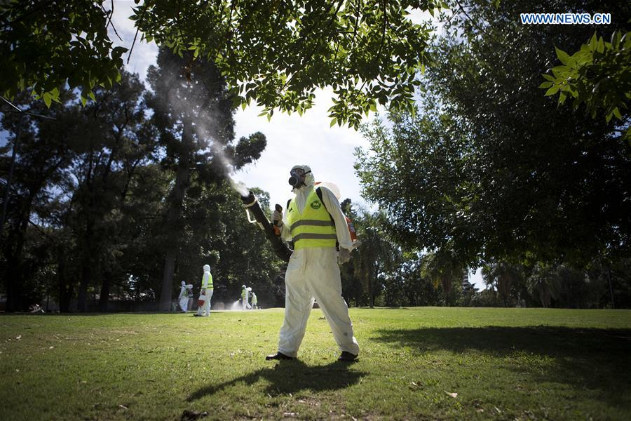 Argentina's Environment and Public Space Ministry fumigation brigade members spay insecticide in an area of Saavedra Park, in an effort to control the Aedes aegypti mosquito, in Buenos Aires, capital of Argentina, on Feb. 11, 2016.