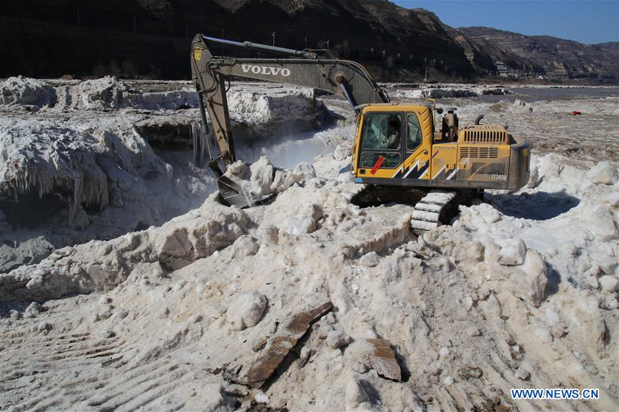 An excavator cleans away ice at the Hukou Waterfall of the Yellow River in Jixian County, north China's Shanxi Province, Feb. 16, 2016.