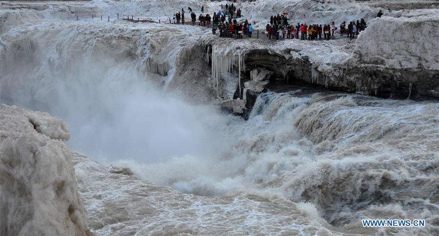 People visit the Hukou Waterfall of the Yellow River in Jixian County, north China's Shanxi Province, Feb. 16, 2016.