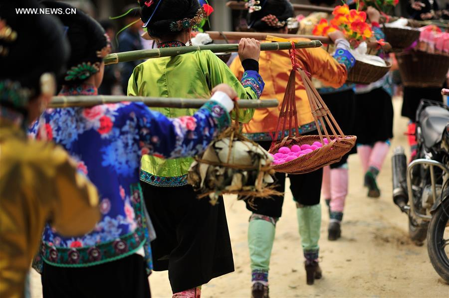 Women of Miao ethnic group carrying gifts on the shoulder walk at Ma'an Village of Congjiang County, Qiandongnan Miao and Dong Autonomous Prefecture, southwest China's Guizhou Province, Feb. 13, 2016.