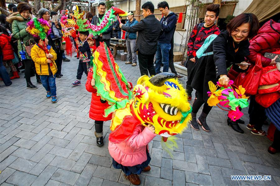 Children experience dragon dance at Ziyuan Art Park in Tianjin, north China, Feb. 21, 2016.