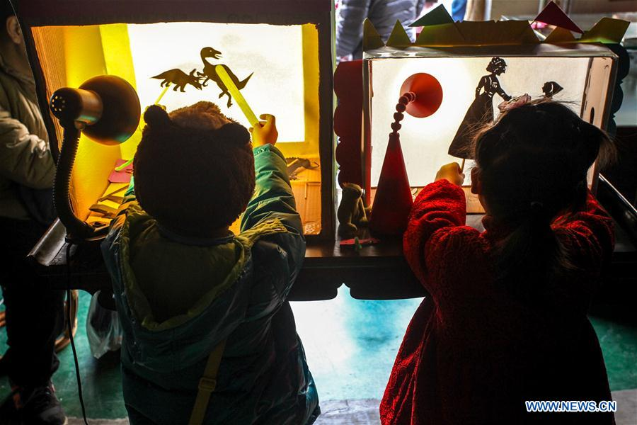 Children play Chinese shadow puppetry at Ziyuan Art Park in Tianjin, north China, Feb. 21, 2016.