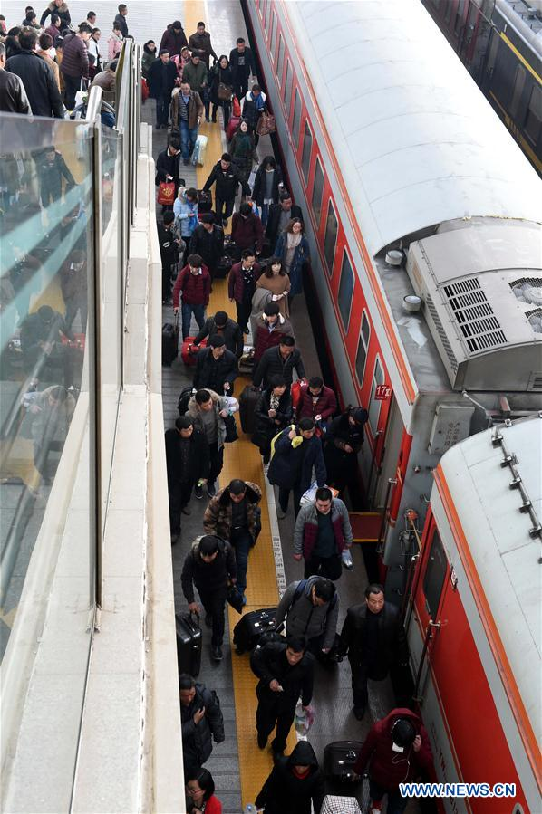Passengers board a train at the railway station of Zhengzhou, capital of central China's Henan Province, Feb. 24, 2016.