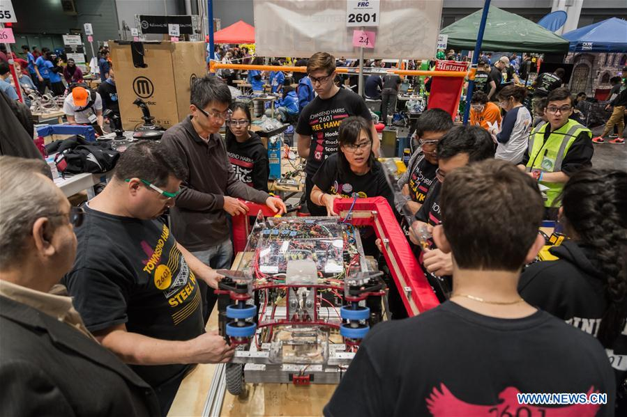 Team members of 'FLYBOTS' from Brooklyn's Paul Robeson High School work on their robot at the 2016 FIRST Robotics Competition New York Regional in Jacob Javits Convention Center in New York City, the United States, March 11, 2016.