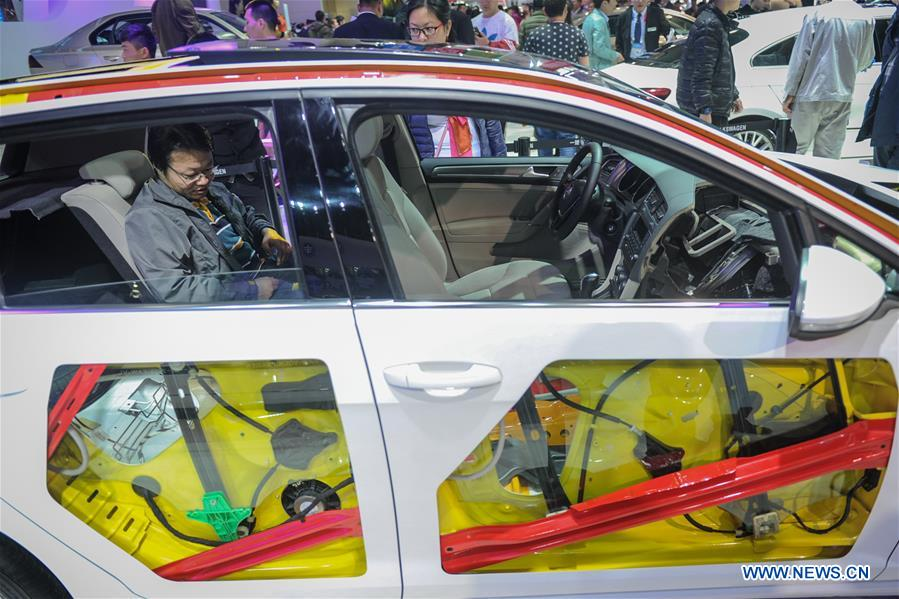 A man experiences a car of Volkswagen during the 11th Harbin spring auto show in Harbin, capital of northeast China's Heilongjiang Province, March 22, 2016.