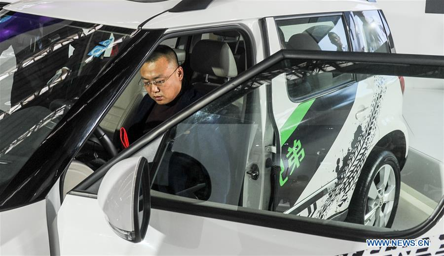 A man experiences a car of Skoda during the 11th Harbin spring auto show in Harbin, capital of northeast China's Heilongjiang Province, March 22, 2016.