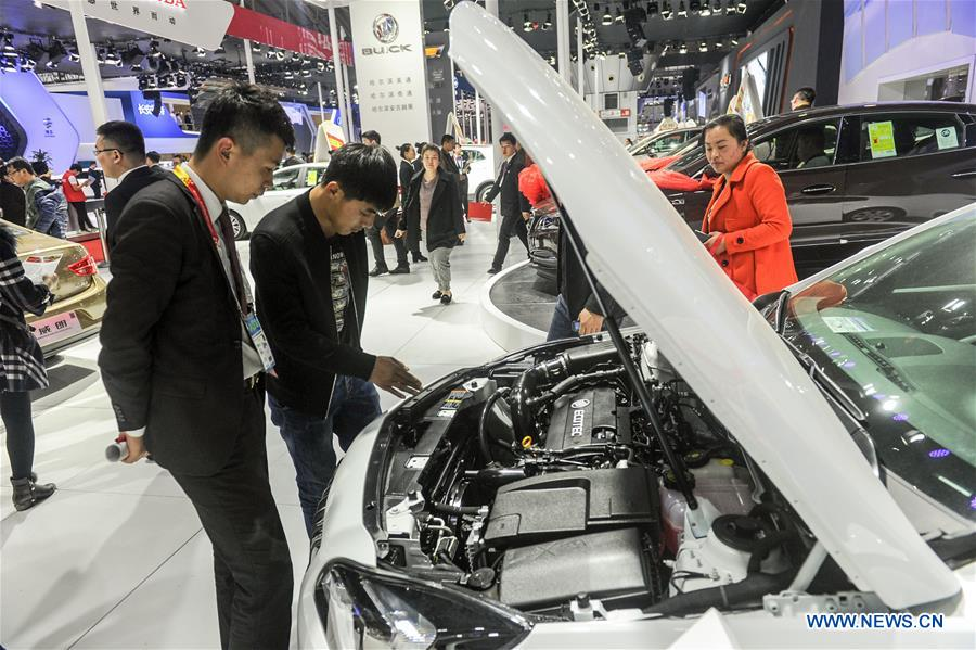 A man views the engine of a Buick auto during the 11th Harbin spring auto show in Harbin, capital of northeast China's Heilongjiang Province, March 22, 2016.