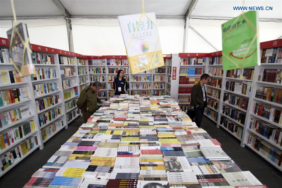 People select books at a book fair in Chaoyang Park in Beijing, capital of China, April 15, 2016.