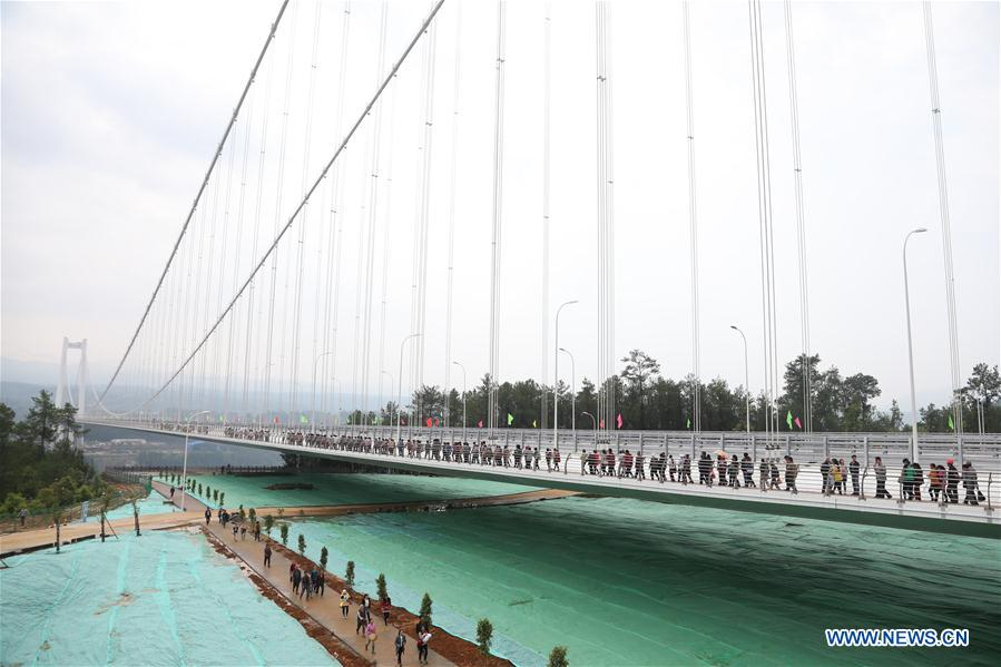 People walk on the newly-opened Longjiang grand bridge in southwest China's Yunnan Province, April 20, 2016.