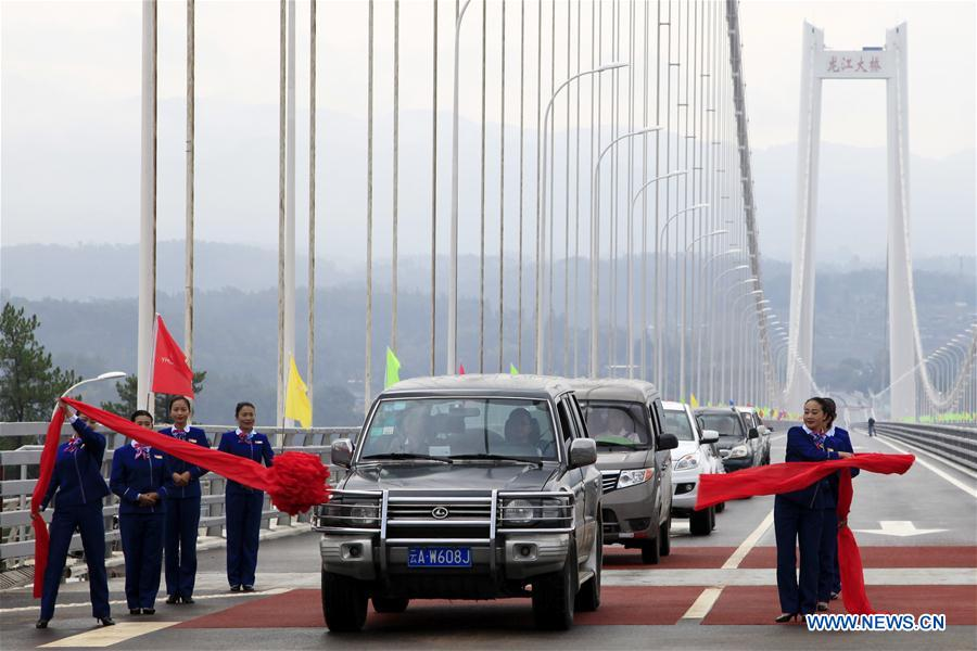 People attend the opening ceremony of Longjiang grand bridge in southwest China's Yunnan Province, April 20, 2016.