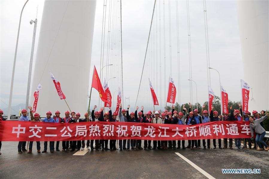 Members of construction units for Longjiang grand bridge celebrate the opening of the bridge in southwest China's Yunnan Province, April 20, 2016.