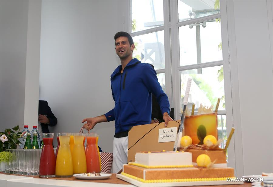 Serbia's Novak Djokovic cuts his birthday cake at the Roland Garros 2016 French Open tennis tournament in Paris, France on May 22, 2016