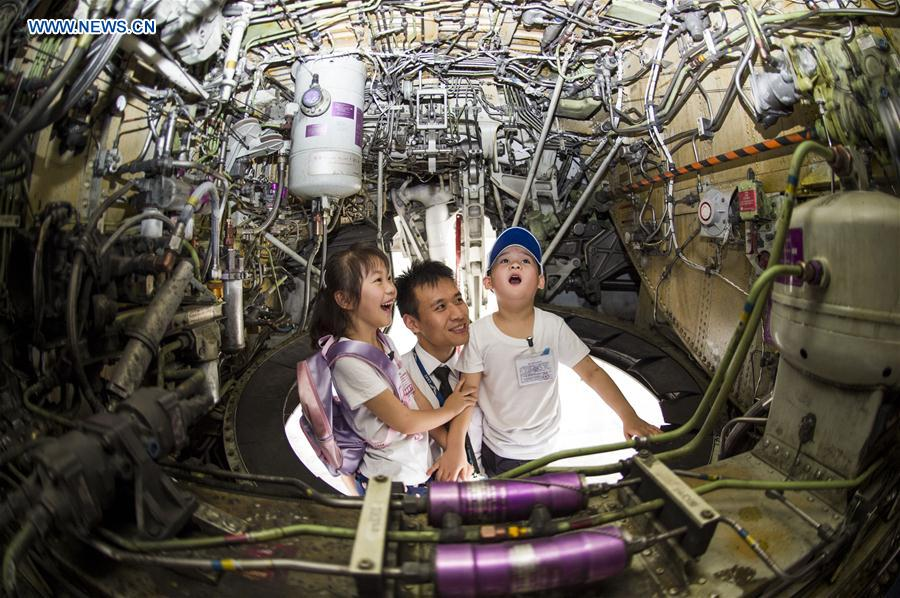 Children are amazed by the interior structure of an airliner during an aviation-themed visit in Wuhan, capital of central China's Hubei Province, May 30, 2016.