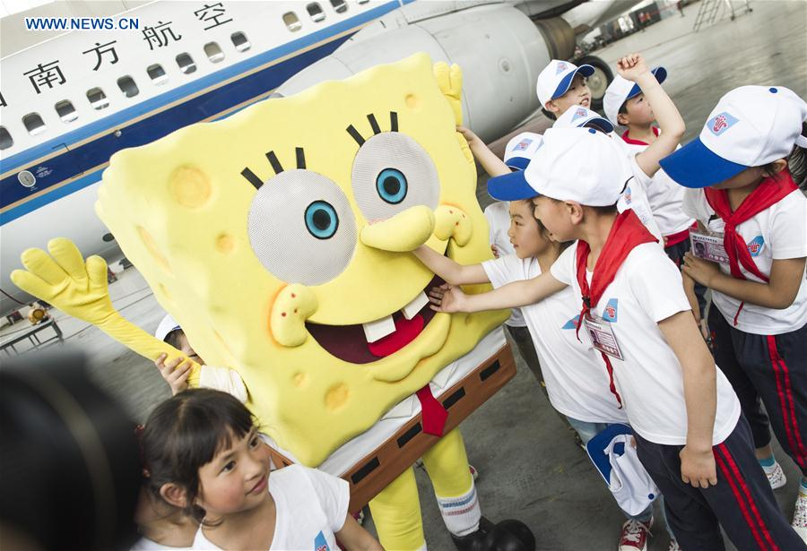 Children interact with a mascot inside a hangar during an aviation-themed visit in Wuhan, capital of central China's Hubei Province, May 30, 2016.
