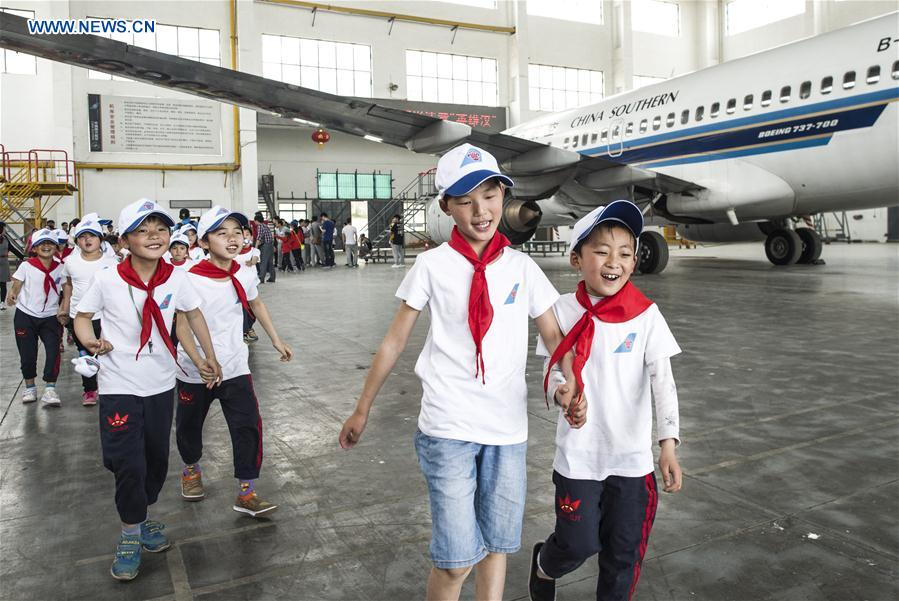 Boys and girls walk inside an airliner gangar as they take part in an aviation-themed visit in Wuhan, capital of central China's Hubei Province, May 30, 2016.