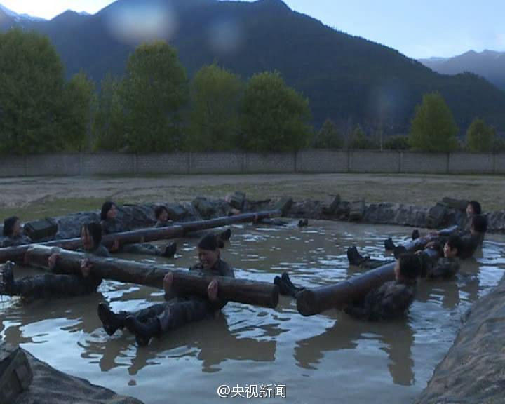 女兵水中抱60余斤圆木仰卧起坐。