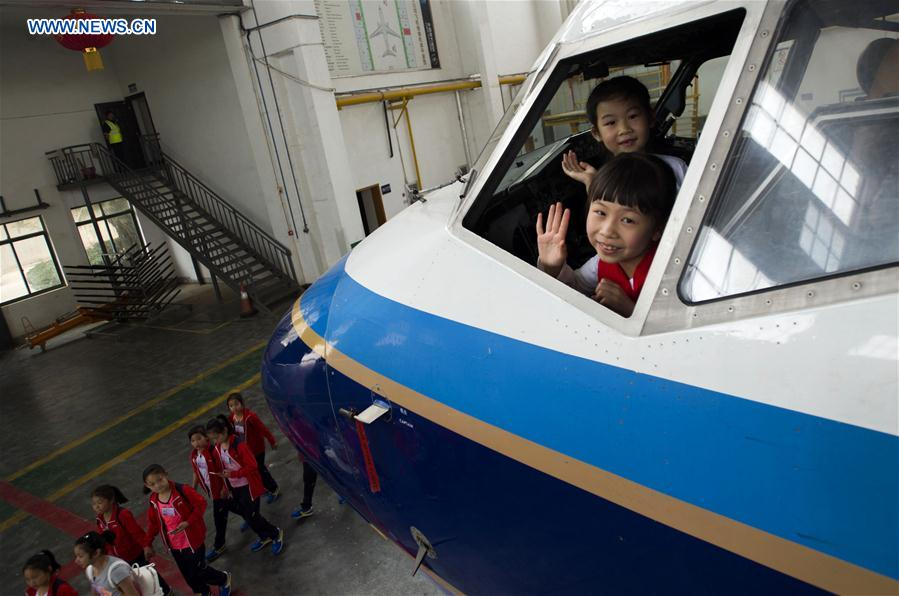 Two girls wave inside an airliner cockpit during an aviation-themed visit in Wuhan, capital of central China's Hubei Province, May 30, 2016.