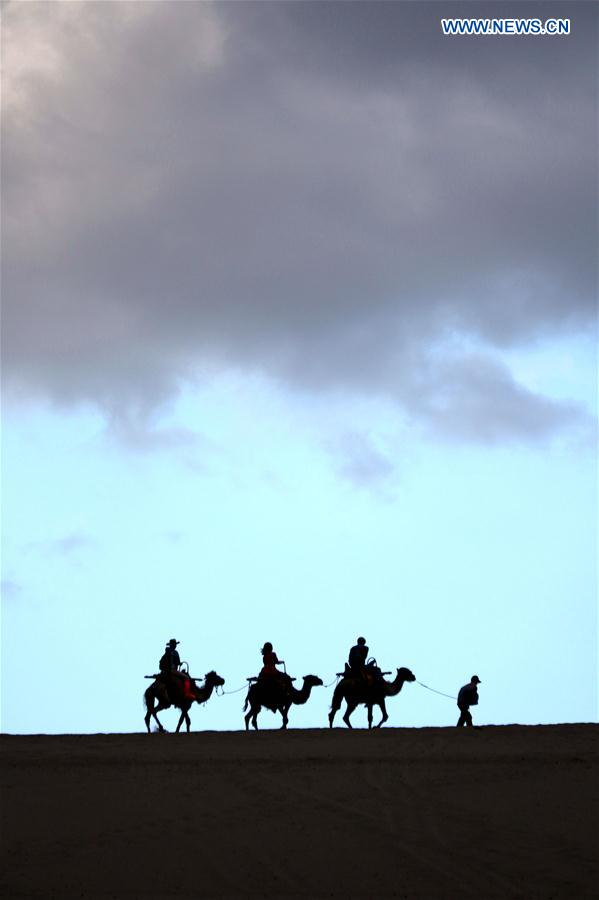 Tourists visit desert scenery in Dunhuang, NW China