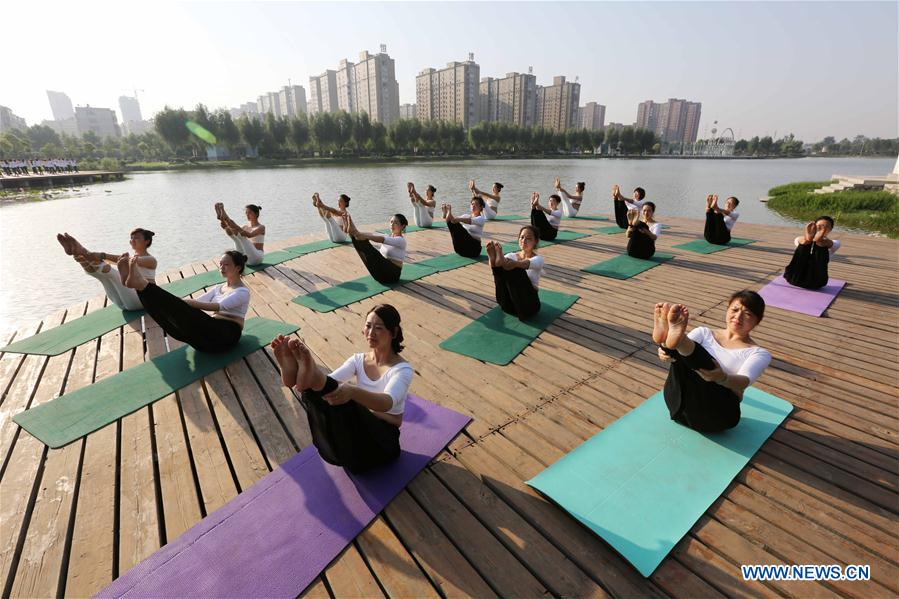 People practise yoga at the Longquan Lake Park in Wuzhi County of Jiaozuo, central China's Henan Province, June 18, 2016.