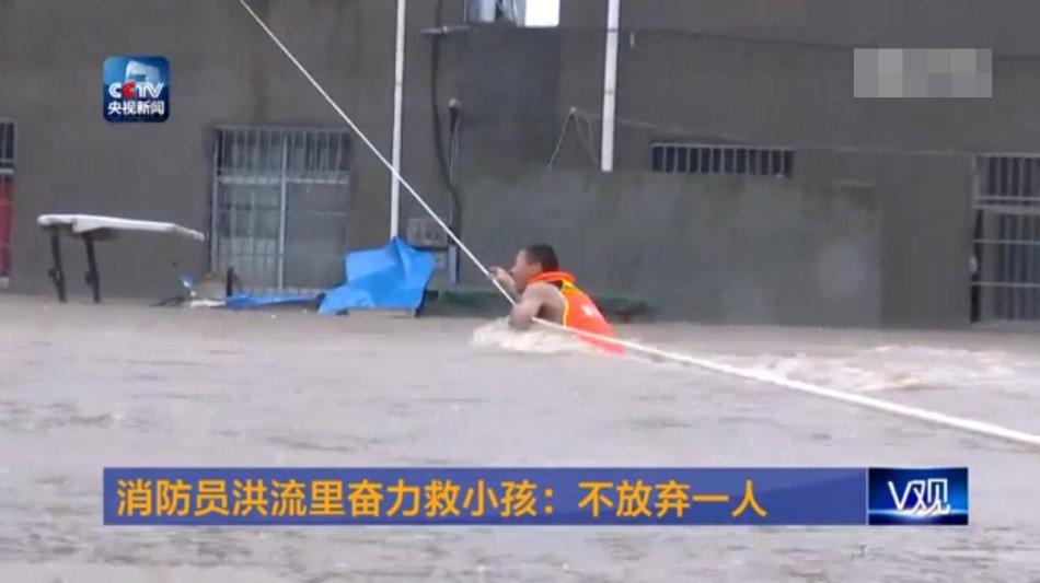 湖北一消防员单手举孩子摸绳逃出洪流