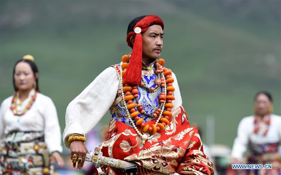 A model presents traditional Tibetan costumes during a fashion show held at Batang grassland of Yushu City of Yushu Tibetan Autonomous Prefecture, northwest China's Qinghai Province, July 26, 2016.