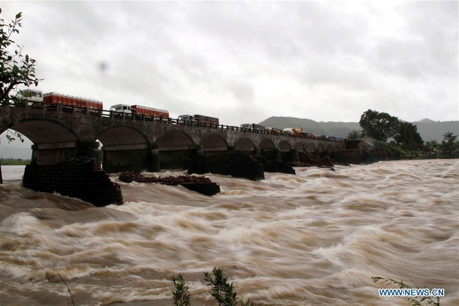 People watch the search operation in the flooded Savitri river after an old bridge collapsed due to torrential rain in Mahad, Indian state of Maharashtra, Aug. 3, 2016.