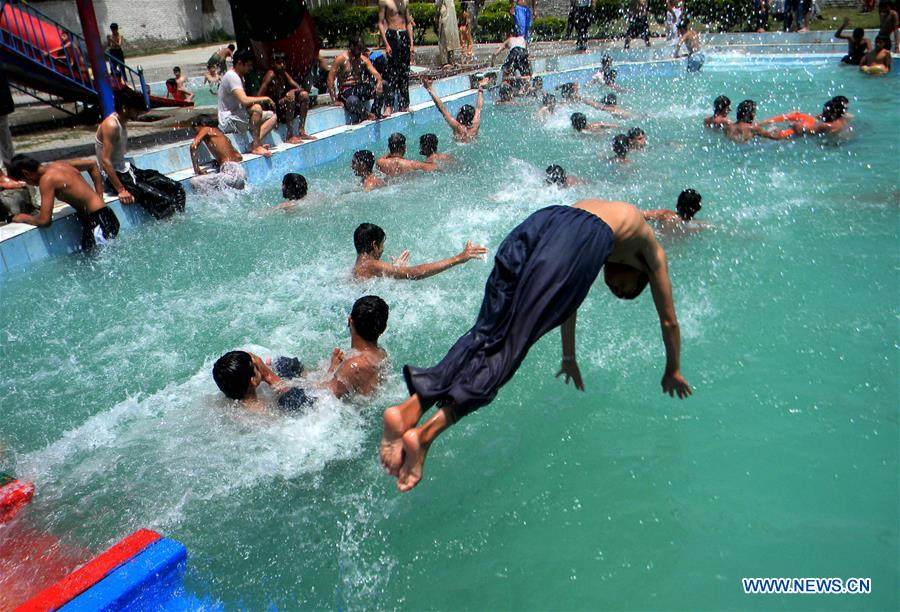 Boys cool themselves off in a swimming pool in northwest Pakistan's Peshawar, on Aug. 5, 2016.