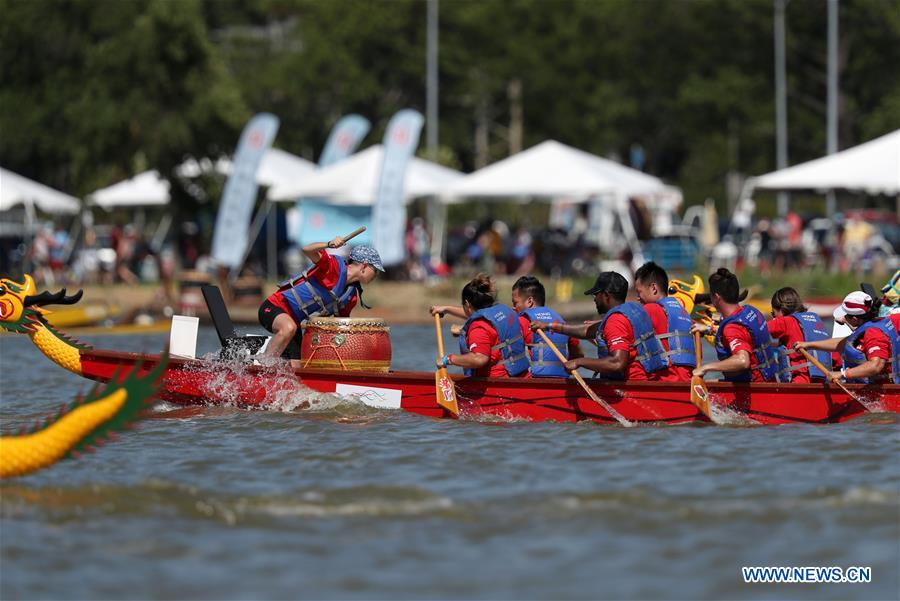 Dragon boat players cheer for the completion of a competition during the Hong Kong Dragon Boat Festival in New York (HKDBF-NY) held in Corona Park of New York, the United States, Aug. 7, 2016.