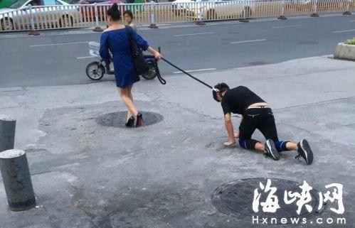女子拉着男子在路上爬行(网友图)