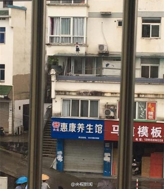 """3岁女童爬上阳台遮雨棚 民警雨中""""飞檐走壁""""救人"""