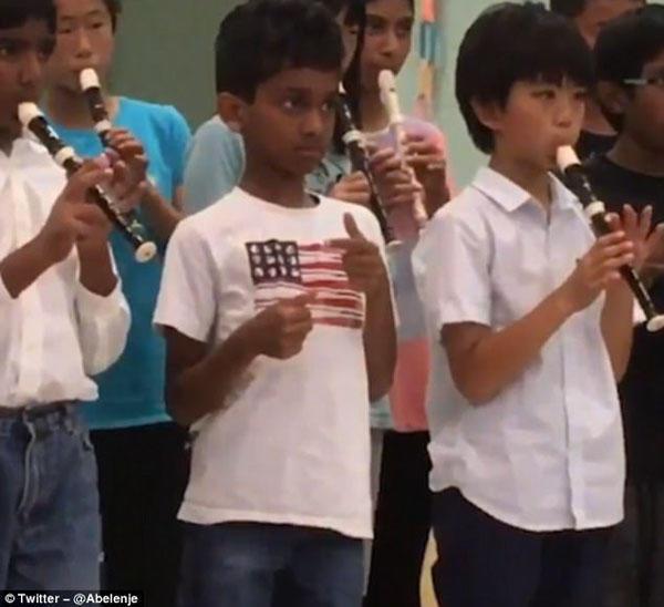 美国男孩忘带乐器 无奈假装演奏走红网络
