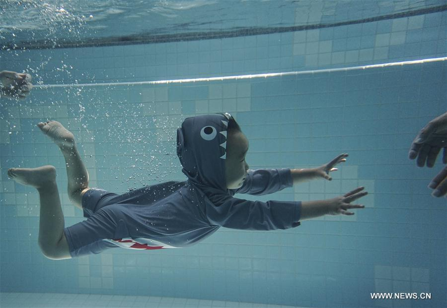 Children dive in water at Loong Swimming Club in Beijing