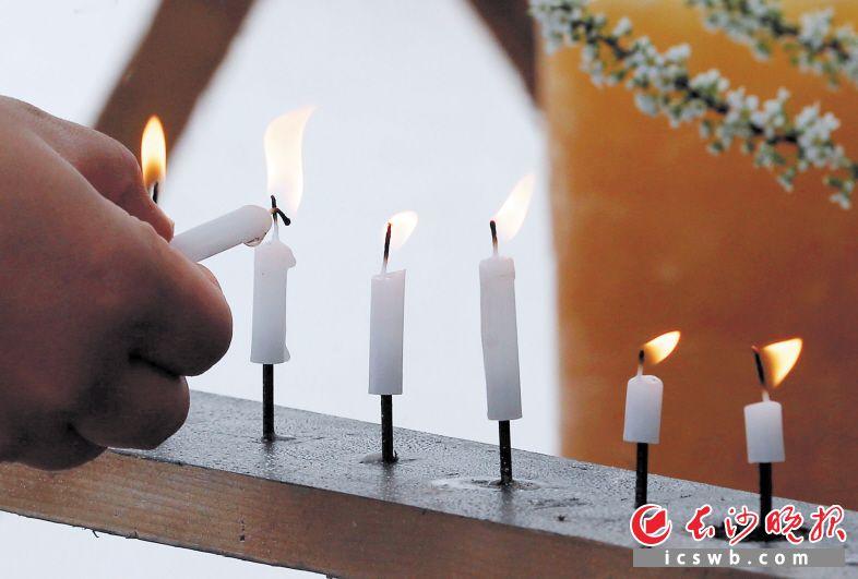 """3月11日,在日本东京的一座公园,一名女子在纪念""""3·11""""大地震的活动上点燃蜡烛。 新华社/路透"""